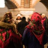KIEV UKRAINA - 14 JANUARI: Unga flickorna i ukrainska traditionella etniska kläder är sjungande lovsånger på gångtunnelstationen Royaltyfri Foto