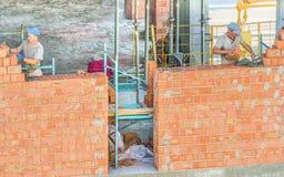 Kiev Ukraina - Juli 16, 2018 Arbetararbete på konstruktionsplatsen Arbete är under väg att lägga en vägg av röd tegelsten Royaltyfri Bild