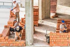 Kiev Ukraina - Juli 17, 2018: Arbetararbete på konstruktionsplatsen Arbete är under väg att lägga en vägg av röd tegelsten Royaltyfria Bilder
