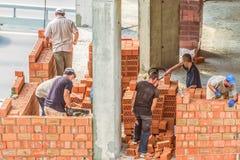 Kiev Ukraina - Juli 17, 2018: Arbetararbete på konstruktionsplatsen Arbete är under väg att lägga en vägg av röd tegelsten Royaltyfri Bild