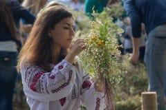 Kiev Ukraina - Juli 06, 2017: Flickan virvlar en krans av örter och blommor på festivalen Royaltyfria Foton