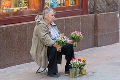 Kiev Ukraina - Juni 16, 2016: Den äldre kvinnan säljer lösa blommor Arkivbilder