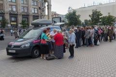 Kiev Ukraina - Juni 19, 2016: Volontärer fördelar mat till hemlöns och fattigt på den Khreshchatyk gatan Arkivbilder