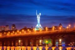 Kiev Ukraina - Maj 04, 2018: Sikt av den Paton bron, fäderneslandmonumentet och den Dnieper floden på natten, härlig cityscape arkivfoto