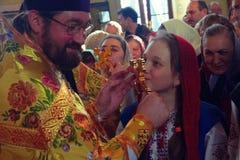 Kiev Ukraina, mars 12 2016 Kiev Ukraina, mars 12, 2016 Unga flickan kysser korset Arkivfoton