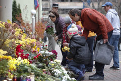 KIEV UKRAINA - November 14, 2015: Folket lägger blommor på den franska ambassaden i Kiev i minnet av offerterrorattackerna i Pari Royaltyfria Bilder