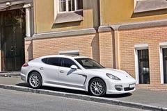 Kiev Ukraina - November 3, 2017; Vita Porsche Panamera som parkeras på trottoaren mot bakgrunden av ett privat hus arkivfoto