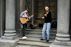 04 18 Kiev 2019 Ukraina Tv? gatamusiker En gitarrist och den andra violinisten p? bakgrunden av d?rrarna av synagen arkivbild