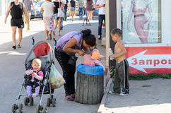 KIEV, UKRAINE – SEPTEMBER 8, 2016: Woman with three little children searching for food in the waste basket near a market. This s Stock Photo