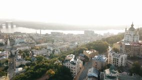 KIev Ukraine aeriel drone view to Andriyivskyy Descent, Podil, St. Andrew`s Church, river Dnepr. Sunrise backlight stock footage