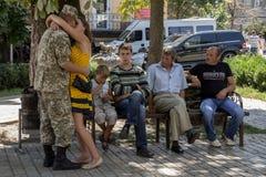 KIEV, UKRAINE - 9 AOÛT 2015 : Soldat ukrainien sur le congé du conflit oriental de l'Ukraine embrassant l'amie à côté des parents Photos stock