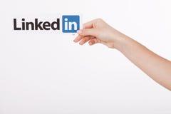KIEV, UKRAINE - 22 août 2016 : La femme remet juger le signe de logo de Linkedin imprimé sur le papier sur le fond blanc Linkedin Image stock