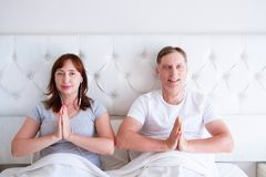 Kiev,Ukraine-09.10.2018: apple earpods. yoga , mindfulness, harmony and people concept - happy middle-aged couple in namaste pose stock images