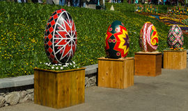 KIEV, UKRAINE - April 17, 2017: Easter eggs. In the foreground there are four huge, painted Easter eggs standing in a row on wooden flower stands, in the Stock Photos