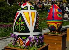 KIEV, UKRAINE - April 17, 2017: Easter folk festival, April 17, 2017, Kiev, Ukraine. In the foreground are two huge, painted Easter eggs, standing on wooden Stock Image