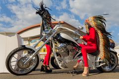 Kiev, Ukraine - April 20, 2018: Girls in Indian costumes and a luxury motorcycle. At the motorcycle exhibition royalty free stock image