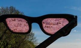 KIEV, UKRAINE - April 17, 2017: Huge rose-colored glasses staring into the sky. Close-up - huge pink glasses against the blue sky, glasses of large glasses Stock Photos