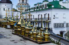 KIEV, UKRAINE - April 17, 2017: The Lavra Crosses. In the foreground there are rows of differently sized domes of dome crosses, in the background the main bell Royalty Free Stock Photography