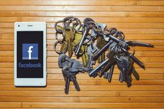 Threat of blocking and banning facebook, encryption keys are located next to the phone. Kiev, UKRAINE - APRIL 2018: threat of blocking and banning facebook Royalty Free Stock Image