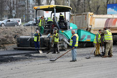KIEV, UKRAINE - APRIL 6, 2017: Workers operating asphalt paver machine and heavy machinery during road repairs.  royalty free stock images