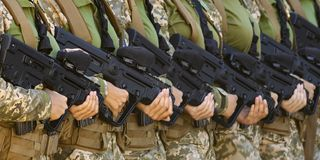 Automatic weapons in female hands royalty free stock photography