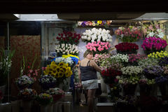 KIEV, UKRAINE - AUGUST 10, 2015: Florist middle aged woman working on her flowers in an underground of Independence - Maidan Squ Stock Photography