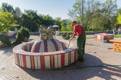 Kiev, Ukraine - August 27, 2016: Male - cleaner cleans the fountain on the playground Royalty Free Stock Images