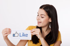 KIEV, UKRAINE - August 22, 2016: Woman hands holding facebook thumbs up sign printed on paper on white background Royalty Free Stock Photos
