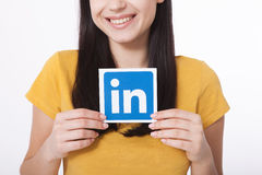 KIEV, UKRAINE - August 22, 2016: Woman hands holding Linkedin icon sign printed on paper on white background. Linkedin Stock Photo