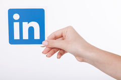 KIEV, UKRAINE - August 22, 2016: Woman hands holding Linkedin icon sign printed on paper on white background. Linkedin Stock Images