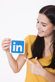 KIEV, UKRAINE - August 22, 2016: Woman hands holding Linkedin icon sign printed on paper on white background. Linkedin Royalty Free Stock Photo