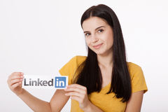 KIEV, UKRAINE - August 22, 2016: Woman hands holding Linkedin logo sign printed on paper on white background. Linkedin Stock Photo