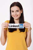 KIEV, UKRAINE - August 22, 2016: Woman hands holding Linkedin logo sign printed on paper on white background. Linkedin Royalty Free Stock Image