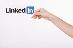 KIEV, UKRAINE - August 22, 2016: Woman hands holding Linkedin logo sign printed on paper on white background. Linkedin Stock Image