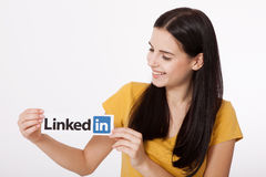 KIEV, UKRAINE - August 22, 2016: Woman hands holding Linkedin logo sign printed on paper on white background. Linkedin Royalty Free Stock Photo