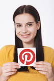 KIEV, UKRAINE - AUGUST 22, 2016: Woman hands holding Pinterest icon printed paper. Is photo sharing website. Stock Photos
