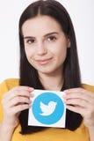 KIEV, UKRAINE - AUGUST 22, 2016: Woman hands holding Twitter logotype icoi bird printed paper. Twitter is an online Stock Image