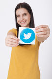 KIEV, UKRAINE - AUGUST 22, 2016: Woman hands holding Twitter logotype icoi bird printed paper. Twitter is an online Royalty Free Stock Image