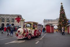 Kiev, Ukraine - December 30, 2018: Children`s attraction in the form of a steam locomotive on a Kontraktova Square. Near the New Year tree royalty free stock images
