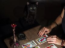 The fortune teller lays out on a wooden table the tarot cards by the light of a lantern and a candle. Black cat sitting near the t. Kiev, Ukraine - December 10 royalty free stock photo