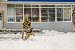 KIEV, UKRAINE - 18 DECEMBER, 2017: Worker cleans sidewalk with snowplow machine after heavy snowfalls.  Stock Photo