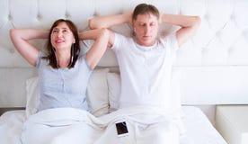 Kiev, Ukraine-09 10 2018 : earpods de pomme Couples âgés moyens heureux détendant sur un lit à la maison et regardant la caméra e photographie stock