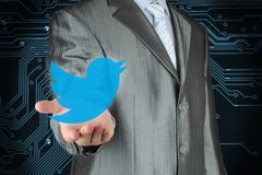 Businessman holds Twitter icon. Kiev, Ukraine - February 12, 2018: Businessman holds Twitter icon on circuit board background. Twitter is a well-known social Royalty Free Stock Image
