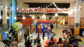 Funny animators in carnival costumes entertain children in the children`s area. Kiev, Ukraine, January 2019: - Funny animators in carnival costumes entertain stock video footage