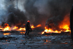 Kiev, Ukraine, January 22, 2014. A young guy, a protester carrie. S tire in fire royalty free stock photo