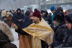 Kiev, Ukraine - 18 janvier 2018 : Le prêtre arrose les paroissiens de l'église avec de l'eau consacré photos stock