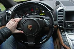 Kiev, Ukraine; July 4, 2013; A man holds the steering wheel of a luxury car. Gold ring on his hand. Porsche Cayenne royalty free stock images