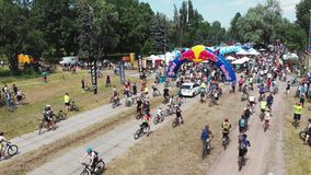 Kiev/Ukraine-June,1 2019 Aerial view of group of young attractive cyclists riding around rest zone in green park with beautiful na stock video footage