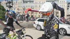 Kiev/Ukraine-June,1 2019 Close up of mountain biker in orange mask and big white helmet looking to camera. Portrait of young boy r stock footage