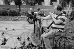 KIEV, UKRAINE - JUNE 8, 2016: Man photographs sitting on his ar Royalty Free Stock Photography